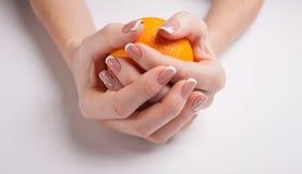härlig manicure Kvinnliga händer rymmer en apelsin royaltyfri fotografi