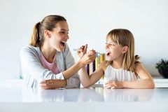 H?rlig matande yoghurt f?r moder och f?r dotter till varandra hemma arkivfoton