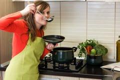 Härlig matlagning och avsmakning för ung kvinna maten royaltyfri bild