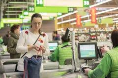 Härlig medelålders kvinna på kontrollen i supermarket Arkivfoto