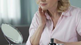 Härlig medelålders kvinna som ser i spegeln och trycker på hennes hud, omsorg arkivfilmer