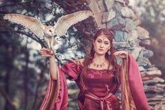 Härlig medeltida kvinna med en flygauggla på hennes hand fotografering för bildbyråer