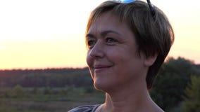 Härlig mellersta ålderkvinna som någonstans ser på solnedgången lager videofilmer