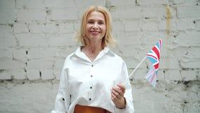 Härlig mellersta åldrig dam som vinkar den brittiska flaggan som ler på bakgrund för tegelstenvägg arkivfilmer