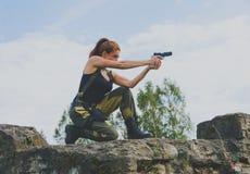 Härlig militär flicka som siktar en pistol Royaltyfri Bild