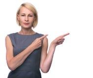 Härlig mitt- åldrig kvinna som pekar fingret i sida Royaltyfri Bild