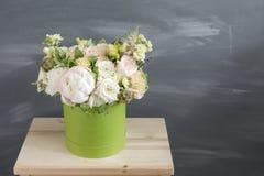 Härlig mjuk bukett av blommor i grön ask på grå bakgrund med utrymme för text royaltyfria bilder