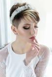 Härlig mjuk elegant ung flickabrud i bröllopsklänning med kronan på huvudet i studio på vit bakgrund med buketten i händer Arkivfoto