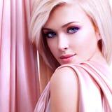 Härlig mjuk kvinna med rosa silke Arkivbilder