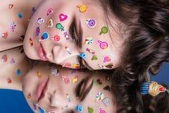 Härlig modeflicka med lyxig yrkesmässig makeup och roliga emojiklistermärkear som limmas på framsidan Arkivfoto
