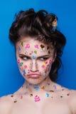 Härlig modeflicka med lyxig yrkesmässig makeup och roliga emojiklistermärkear som limmas på framsidan Arkivbild