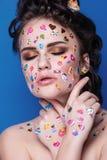Härlig modeflicka med lyxig yrkesmässig makeup och roliga emojiklistermärkear som limmas på framsidan Arkivbilder