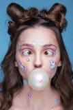 Härlig modeflicka med roliga yrkesmässiga makeup- och emojiklistermärkear som limmas på framsidan Arkivbild
