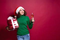 Härlig modekvinna i den Santa Claus hatten Varm ask för gåva för jultröjainnehav på royaltyfri foto