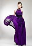 Härlig modekvinna i den violetta långa klänningen Royaltyfri Bild