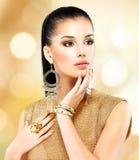 Härlig modekvinna med svart makeup och guld- manikyr Arkivbild