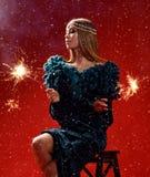 Härlig modekvinna som rymmer två tomtebloss i mörker - grön klänning på röd jul Arkivbilder