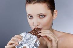 Härlig model ätachoklad, i studion Royaltyfri Fotografi