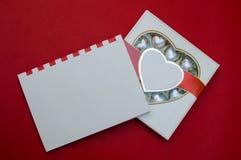 Härlig modell för valentindag Romantisk ask av sötsaker och den moderna anmärkningsboken på den röda bakgrunden Arkivfoto