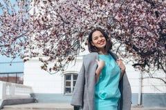 Härlig modell i blå klänning och grått lag av våren som blommar trädet royaltyfria foton
