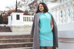 Härlig modell i blå klänning och grått lag på stadsgatan royaltyfri foto