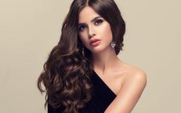 Härlig modell med den länge, täta och lockiga frisyren royaltyfria bilder