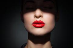 Härlig modell med ljusa röda kanter och framsidahalvan som täckas i skugga Arkivfoto