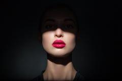Härlig modell med ljusa rosa kanter och framsidahalvan som täckas i skugga Arkivfoto