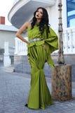 Härlig modell med mörkt hår i lyxig grön klänning royaltyfri bild