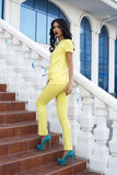 Härlig modell med svart hår som bär den eleganta gula dräkten fotografering för bildbyråer