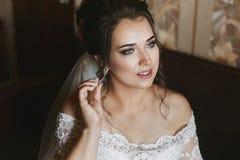 Härlig modell plus format i en trendig bröllopsklänning och med den stilfulla gifta sig frisyren som för justerar hennes örhänge arkivfoton