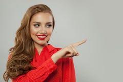 Härlig modell som åt sidan pekar på vit bakgrund Le kvinnan i röd blusstående fotografering för bildbyråer