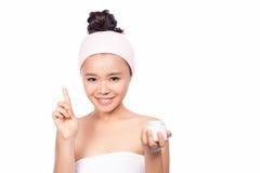 Härlig modell som applicerar kräm- behandling för skönhetsmedel på hennes framsida på vit Arkivfoto