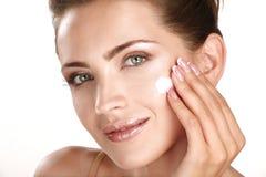 Härlig modell som applicerar kräm- treatmen för skönhetsmedel på henne framsida Royaltyfria Bilder
