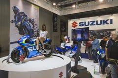 Härlig modell som poserar på den Suzuki mopeden på EICMA 2014 i Milan, Italien Arkivfoton