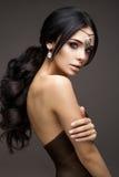 Härlig modellbrunett med långt krullat hår Fotografering för Bildbyråer