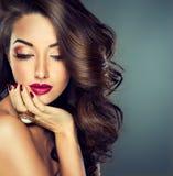 Härlig modellbrunett med långt krullat hår royaltyfria bilder