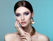 Härlig modemodell som bär eleganta smycken i färgljus arkivbild