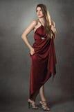 Härlig modemodell som poserar i elegant röd klänning Arkivfoton