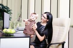 Härlig moder med hennes gulliga dotter på arbetsplatsen arkivbild