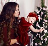 Härlig moder med lyxigt mörkt hår som poserar med hennes gulliga liten flicka bredvid julgranen Fotografering för Bildbyråer