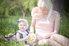Härlig moder och dotter på gräset Royaltyfria Bilder