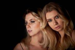 Härlig moder- och dotterstående i studio på svart bakgrund Se utmärkt Yrkesmässig Makeup royaltyfri foto