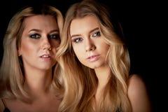 Härlig moder- och dotterstående i studio på svart bakgrund Se utmärkt Yrkesmässig Makeup fotografering för bildbyråer