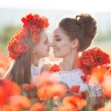 Härlig moder och hennes dotter som spelar i vårblommafält royaltyfri foto