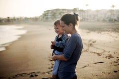Härlig moder och son som spelar på stranden Fotografering för Bildbyråer