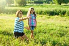 Härlig moder utomhus med det lyckliga dotterbarnet Arkivbild