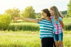 Härlig moder utomhus med det lyckliga dotterbarnet kvinnan visar lite flickan ett finger i avståndet älska för familj royaltyfria bilder