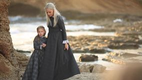 Härlig moderblondin i en lång grå klänning med hennes lilla dotter i en klänning på stranden