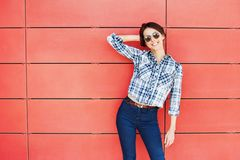 Härlig moderiktig modell som poserar mot den röda väggen royaltyfri bild